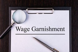 Text WAGE CARNISHMENT is written on a notebook with a pen and a magnifying glass lying on the table. Business concept.