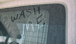 Text wash me written on the car