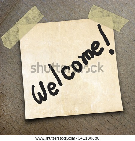 text welcome on short note paper on the packing paper box texture background