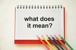 text what does it mean written on notepad with pencils and white background. High quality photo