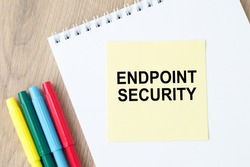 text writing Endpoint Security. Concept meaning the methodology of protecting the corporate network. On the table is a notebook with a yellow card for notes and colored markers