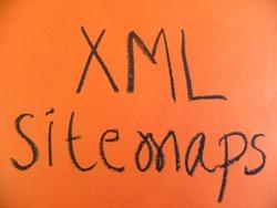 Text XML sitemaps hand written by black oil pastel on orange color paper