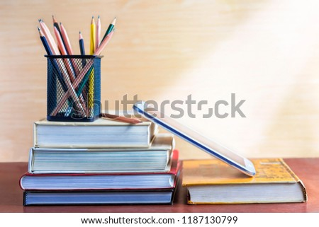 Textbook, pencil, and notepad on the table. The concept of combining learning in the past and present.