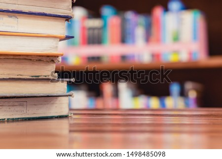 Textbook stack on wooden table with blur background of bookshelf in library with copy space. Photo concept of education, knowledge, traditional learning, and literature. Selective Focus