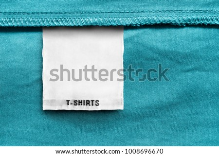 Textile clothes label lettered t-shirts on blue cotton background