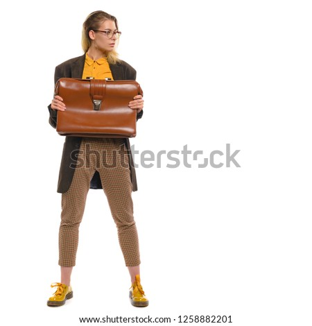 facc77412d4b7 Fashionable teenager girl in glasses in a brown jacket, checkered pants,  yellow