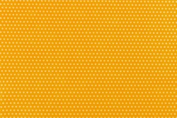 Textile homogeneous background color yellow in white fine polka dots, horizontal pattern. View from above. Emotionally warm sunny mustard sandy saturated.