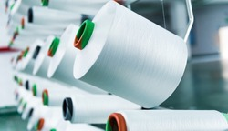 Textile industry - yarn spools on spinning machine.