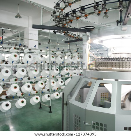 Textile industry - yarn spools on spinning machine in a textile factory