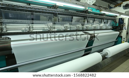 Textile industry - yarn spools on spinning machine in a textile factory Rolls of industrial cotton fabric for clothing cloth textile manufacture on machine Bottom view of machinery and equipment in a