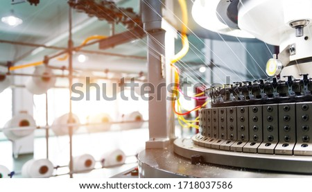 Textile industry - yarn spools on spinning machine in textile factory.