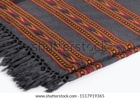 Textile plaid with ornament on wooden background. Colorful plaids, close-up. Homeliness, copy space.