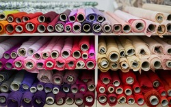 Textile retail store, drapery or drapery shop. Close-up colorful linen fabric rolls in pink, orange, beige, purple colors. E-commerce, offline sale, tailor or atelier concept. High quality image