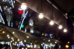 textile visor on the canopy with string lamps lighting the night city restaurant terrace with an umbrella and garlands close-up.