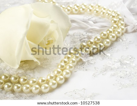 Textile wedding background with white rose and pearls