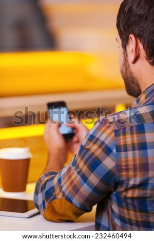 Texting message to friend. Rear view of man texting on his mobile while sitting in coffee shop