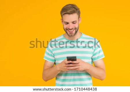 Texting SMS message. Happy guy send sms via smartphone yellow background. Sms messaging. Short message service. New technology. Mobile lifestyle. Modern life. Trusted SMS delivery.