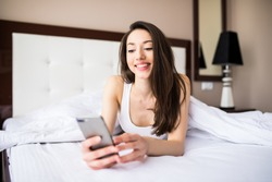 Texting to friend. Beautiful young woman smiling and holding smart phone while lying in the bed at home