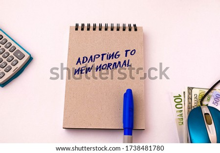 Texts embracing new normal note pad. Conceptual of adapting to new norm and lifestyle change due to  Covid-19. Calculator, pen and mouse on right in visibility.  Selective focus on note pad cover. Photo stock ©