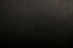 Textural black wall. Black background with a clearly visible texture. Dark background, abstraction, scratches.