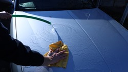 textural movement of water on a clean hood of a gray car during washing by hand using a hose and a suede cloth to clean the vehicle from light dirt