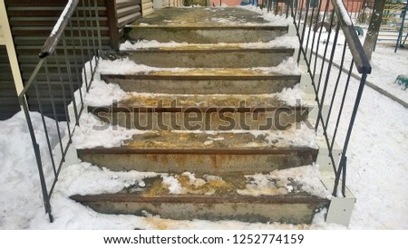 Texture and background of old concrete steps with rusty metal inserts with snow near a public building in the daytime in the winter time of day. #1252774159