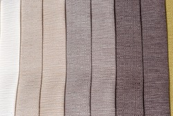Texture and detail of opaque soft tones of brown, yellow gold and off white interior decoration sample color swaps of textured curtain fabric for comparison and feel