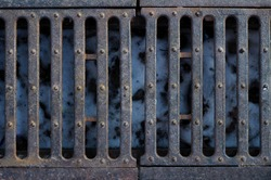 Texture background: city street brown old rusty metal iron gutter. Gray drain grate for waste and rain water