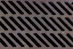 Texture background: city street brown old rusty metal iron gutter. Gray drain grate for waste and rain water.