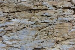 Texture, background layers and cracks in sedimentary rock on cliff face. Cliff of rock mountain. Rock slate in the mountain. Seamless abstract background. Cracks and layers of sandstone