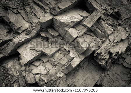 Texture, background layers and cracks in sedimentary rock on cliff face. Cliff of rock mountain. Rock slate in the mountain. Seamless abstract background. Cracks and layers of sandstone.