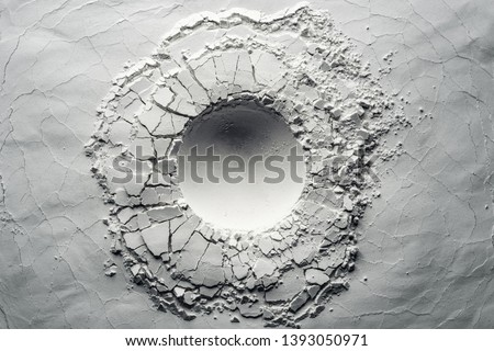 Texture background of an impact crater. Background usable for still life photography. White powder texture with round impact crater. Minimalism flat lay.