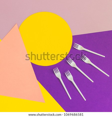 Texture background of fashion pastel colors: yellow, pink and purple geometric pattern papers and plastic forks. Triangles and circles. 90s style  #1069686581
