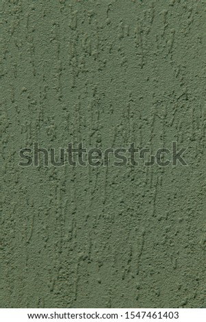 Texture background of rough green rough surface. Painted wall with bulges. Close-up, vertical, cropped shot. The concept of design and construction.