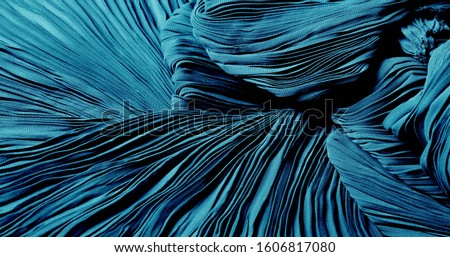 Texture, background, pattern, Cloth pleated blue. A shiny finished folded satin fabric is a light, glossy glossy and beautiful type of fabric that makes the design of the end stylish and glamorous Stockfoto ©