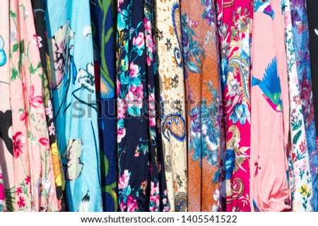 Texture background, pattern. Different fabrics stacked on a table in a pile