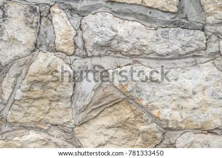 Texture, background, pattern. Old granite stones. An old stone wall. Texture of a stone wall. Brick wall from an old gray stone and sandstone texture background. #781333450