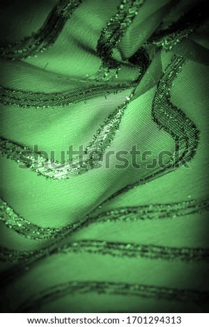 texture  background picture the fabric is transparent emerald green with brightly innate stripes, the material allowing the light to pass through it so that the objects behind are clearly visible.