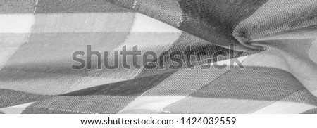 Texture, background, silk scarf feminine black and white with a metal stripe. The scarf is decorated with a delicate patchwork pattern in pastel colors with abstract Scottish motifs. checked fabric #1424032559