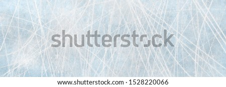 Texture blue ice surface with scratches of skates as background for advertising surfaces in winter