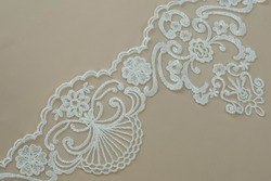 Texture lace fabric. lace on white background studio. thin fabric made of yarn or thread. a background image of ivory-colored lace cloth. White lace on beige background.