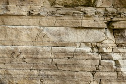 Texture, layers and cracks in sedimentary  rock on cliff face.