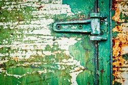 Texture metal door with hinge detail. Rusty door with cracked paint. Green painted door.