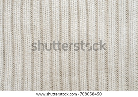 b8124dea263 Texture of a beige knitted sweater close-up. Vertically oriented pigtails  on knitted fabric