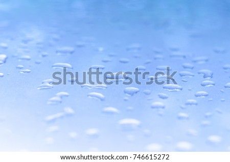 texture of a drop of water on a blue glossy surface #746615272