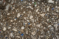 Texture of a lot of grey rubble, small mini pebbles and pieces of broken  small colored glass. Textural background. Natural background. View from above