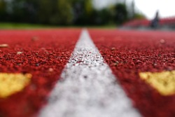 Texture of a red rubber running track with a white stripe in the middle. Selective focus, blur. Running track at the stadium close up