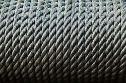 Texture of a spiral black rope wound on a drum, close up