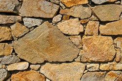 Texture of a stone wall. Textured background of the stone wall of the old castle. Stone wall as background or texture. Part of a stone wall, for background or texture