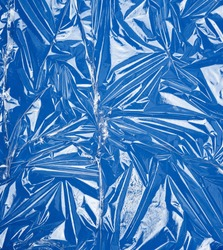 texture of a transparent stretching plastic film for packaging products on a blue background, full frame, close up
